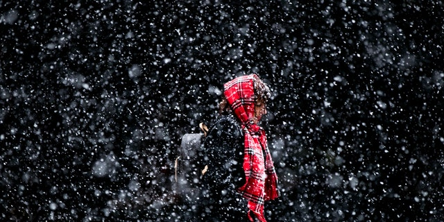 In this March 10, 2017 file photo, a woman walks through a winter snow storm in Philadelphia