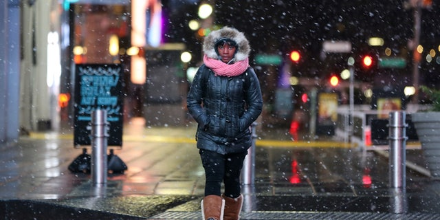 A woman walks as snow falls in Times Square in Manhattan in New York City, New York, U.S., March 7, 2018.