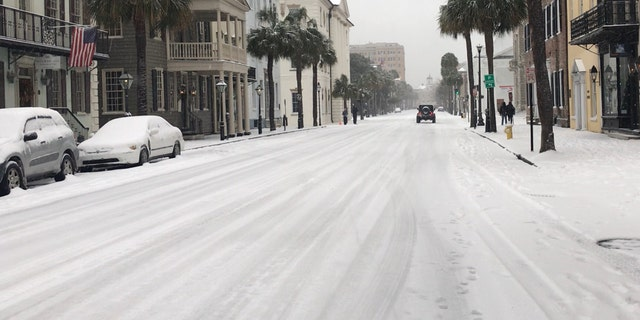 Snowfall in downtown Charleston left streets and cars covered.