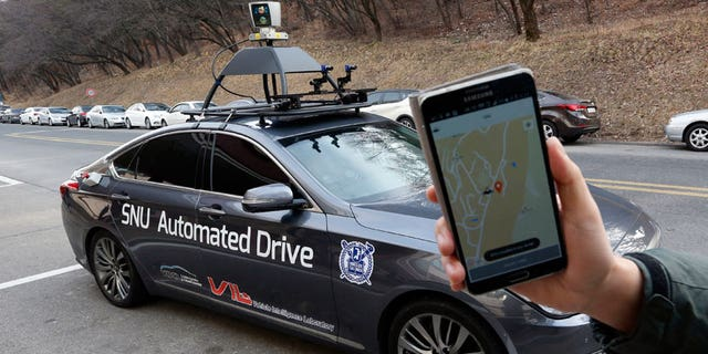 A researcher from the Intelligent Vehicle IT Research Center at Seoul National University shows the smartphone application for the driverless car called Snuber with a fixture on its roof with devices that scan road conditions.