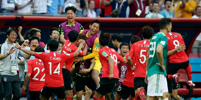 South Korea players celebrate after their teammate Kim Young-gwon scored their side's first goal during the group F match between South Korea and Germany.