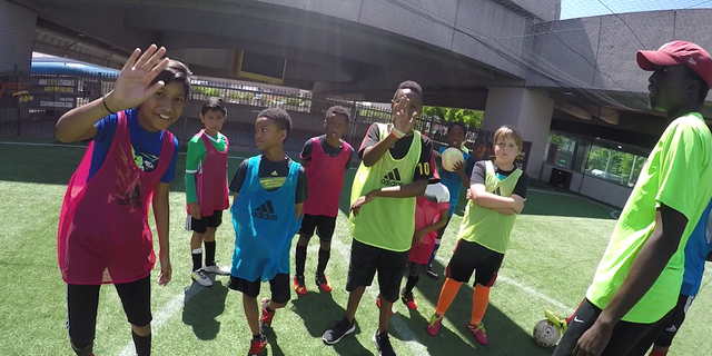 Station Soccer players wave at their friend, who is wearing a GoPro on his head, at their Sunday afternoon practice.