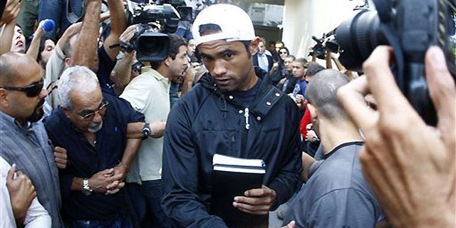 July 8: Flamengo's goalkeeper Bruno Souza walks from a police station to Gericino prison as he is surrounded by police and members of the press in Rio de Janeiro.