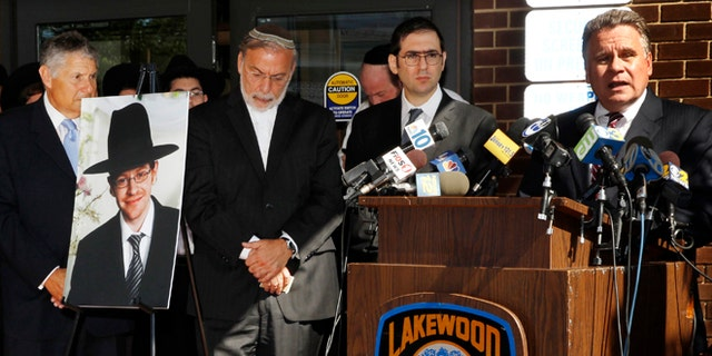Aug. 26, 2014: U.S. Rep. Chris Smith, right, R-NJ, addresses a gathering as he stands near a photograph of Aaron Sofer, center, 23, in Lakewood, N.J. (AP/Mel Evans)