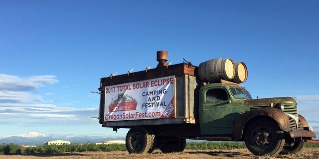 FILE - In this June 13, 2017, file photo, an advertisement for a central Oregon festival built around the Aug. 21 total solar eclipse sits alongside a busy road leading into Madras, Ore. Traffic is already a headache in central Oregon as thousands of people arrive before Monday's total solar eclipse. (AP Photo/Gillian Flaccus, File)