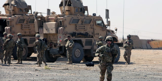 A U.S. soldier runs at a coalition forces forward base near West Mosul, Iraq this past June.