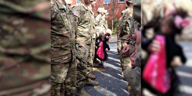 A young girl runs into the Savannah St. Patrick's Day parade to plant a kiss on a soldier.