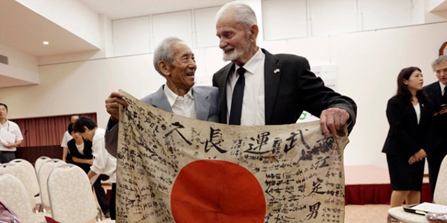 WWII veteran Marvin Strombo, right, and Tatsuya Yasue, 89-year-old farmer, hold a Japanese flag with autographed messages which was owned by his brother Sadao Yasue, who was killed in the Pacific during World War II. Strombo has returned to the fallen soldier's family the calligraphy-covered flag he took from the man's body 73 years ago.
