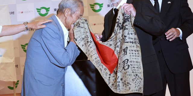 WWII veteran Marvin Strombo, center, returns Tatsuya Yasue, left, a Japanese flag with autographed messages which was owned by his brother Sadao Yasue, who was killed in the Pacific during World Work II, during a ceremony in Higashishirakawa.