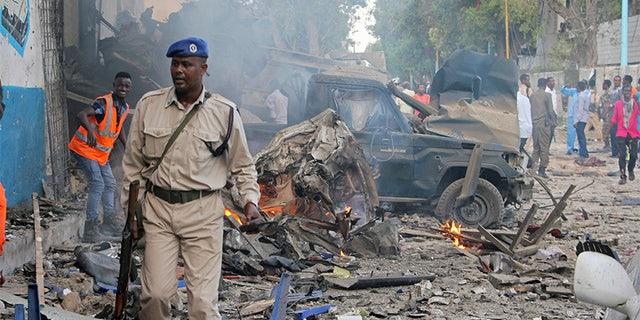 Somali soldier walks near wreckage of vehicles after a car bomb was detonated in Mogadishu, Somalia Saturday,.