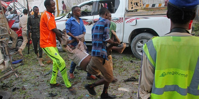 Somalis carry away the wounded civilian who was injured in a car bomb that was detonated in Mogadishu, Somalia, Saturday.