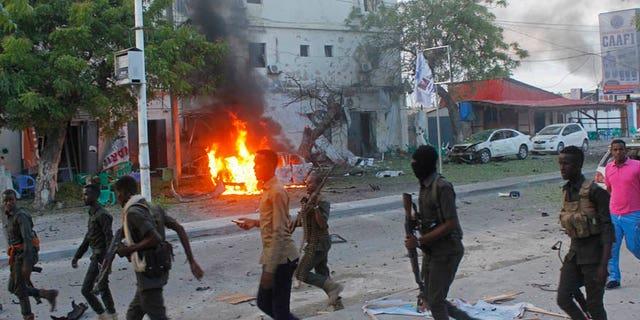 May 8, 2017: Somali security walk near a burning car after a car bomb attack on a restaurant in Mogadishu, Somalia.