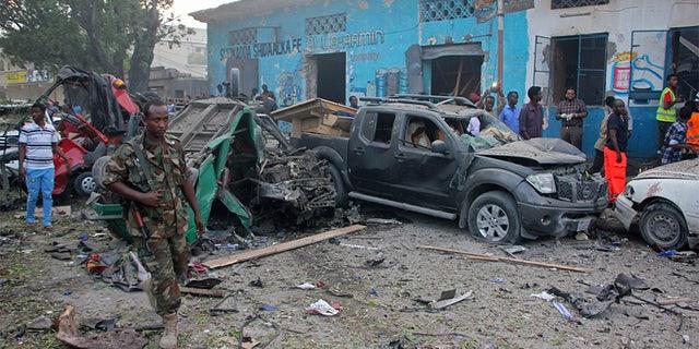 Somali soldier walk near wreckage of vehicles after a car bomb was detonated in Mogadishu, Somalia, Saturday.