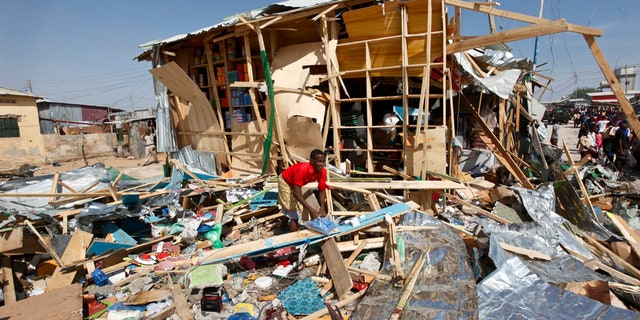 A shopkeeper surveys the wreckage of shops destroyed by a blast in a market in the capital Mogadishu, Somalia Sunday, Feb. 19, 2017. A Somali police officer says a blast at a busy market in the western part of Somalia's capital tore through shops and food stands and killed more than a dozen people and wounded many others. (AP Photo/Farah Abdi Warsameh)