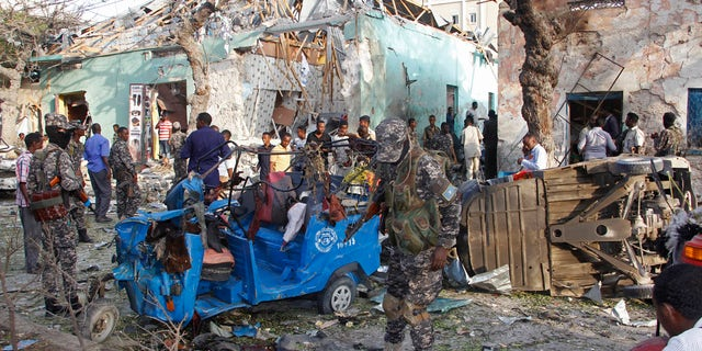 Somalis stand outside a destroyed building after a car bomb in Mogadishu, Somalia Thursday, March 22, 2018.