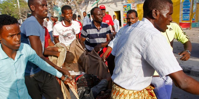 Somalis help a wounded civilian after a car bomb exploded in Mogadishu, Somalia Thursday, March 22, 2018.