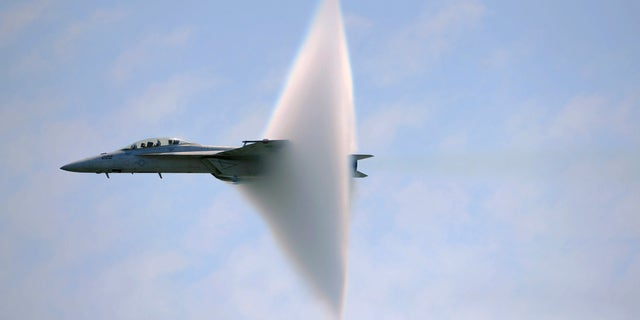 A ring of water vapour is created around pilot Lt. Justin Halligan (L) and Lt. Michael Witt (R) as they fly their F/A-18F Super Hornet airplane within 200mph of breaking the sound barrier while performing at New York Air Show at Jones Beach in Wantagh, New York, May 23, 2009