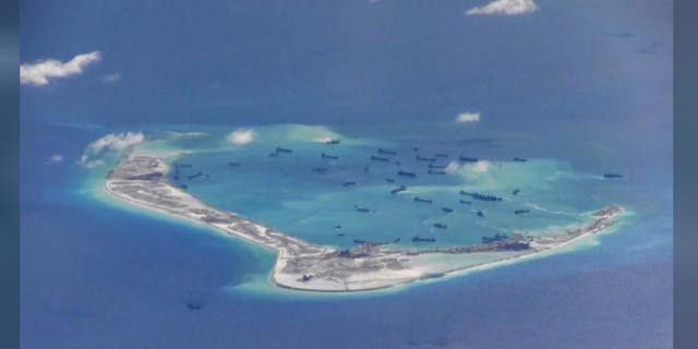 Chinese dredging vessels are purportedly seen in the waters around Mischief Reef in the disputed Spratly Islands in the South China Sea in this still image provided by the United States Navy May 21, 2015.