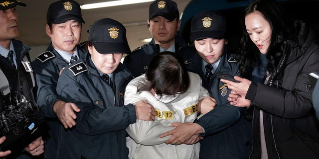 Choi Soon-sil, center, the jailed confidante of disgraced South Korean President Park Geun-hye, arrives for questioning into her suspected role in political scandal at the office of the independent counsel in Seoul, South Korea, Saturday, Dec. 24, 2016.