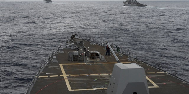 This image provided by the U.S. Navy, taken Oct. 17, 2016, shows the guided missile destroyer USS Decatur, right, pulling into position behind the Military Sealift Command USNS Matthew Perry, during a replenishment-at-sea, seen from the bridge of the guided-missile destroyer USS Spruance, in the South China Sea.