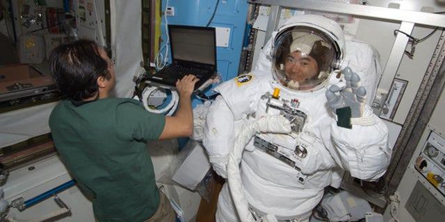Japanese astronaut Akihiko Hoshide of JAXA waves while testing his spacesuit inside the International Space Station ahead of an Aug. 30, 2012 spacewalk with crewmate Sunita Williams of NASA. NASA astronaut Joe Acaba (left) assists.