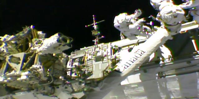 In this frame from NASA TV, Astronauts Mark Vande Hei, left, and Randy Bresnik work on the International Space Station on Thursday, Oct. 5, 2017. The astronauts went out on a spacewalk to give the International Space Station's big robot arm a new hand.