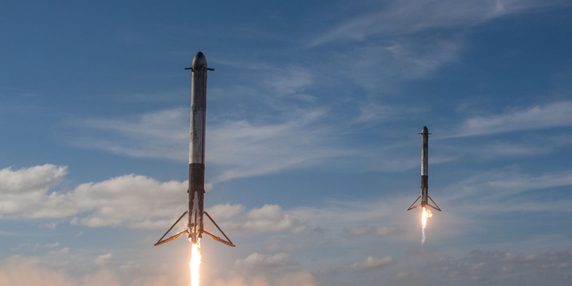 "Two SpaceX Falcon Heavy boosters make a simultaneous landing after launching the first Falcon Heavy rocket into orbit on Feb. 6, 2018. Elon Musk says SpaceX will soon try to land the upper stage of its workhorse Falcon 9 rocket using a ""giant party balloon."""