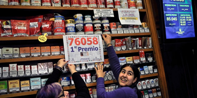 """Dec. 22, 2012: Laura Leon, 30, right, and Pili Medina, 48,  who sold one of the winning lottery tickets with the numbers, 76058, of the top prize of Spain's Christmas lottery known as """"El Gordo,"""" celebrates in her lottery shop in the small town of Tudela, northern Spain."""