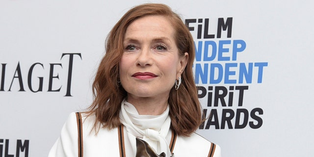"""Isabelle Huppert poses with her award for best female lead for """"Elle"""""""