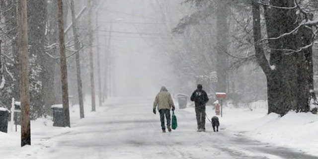 Bryan Gatneau, left, and David Baldwin, with his dog Winni walk home through the snow Tuesday, April 26, 2016, in Bethlehem, N.H.