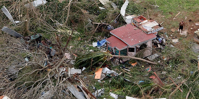 A man stands outside a destroyed home in this aerial photo from a Marine Corps MV-22 Osprey surveying the aftermath from Hurricane Maria in St. Croix, U.S. Virgin Islands, last Thursday.
