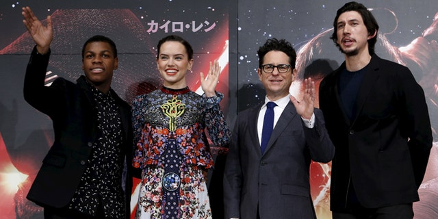 Director J.J. Abrams (2nd R), cast members John Boyega (L), Daisy Ridley (2nd L), and Adam Driver pose for pictures in Tokyo on December 11, 2015.