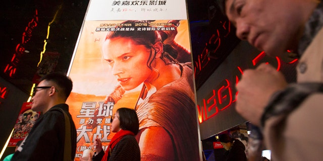 "Jan 9, 2016. People walk past a poster for the new ""Star Wars"" movie at a movie theater in Beijing, China."