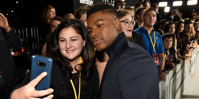 """""""Star Wars: The Last Jedi"""" cast member John Boyega poses for a photo with Olivia Sava, 14, of New York, at the premiere of the film at the Shrine Auditorium in Los Angeles."""