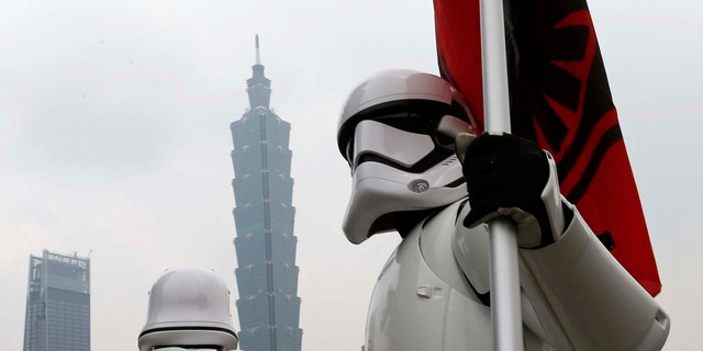 """File photo - Fans dressed as Storm Trooper from """"Star Wars"""" pose in front of landmark building Taipei 101 during Star Wars Day in Taipei, Taiwan May 4, 2017. (REUTERS/Tyrone Siu)"""