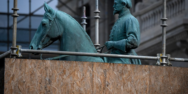 A monument to Confederate General John Hunt Morgan stands encased in a protective scaffolding because of local construction, outside the Historic Lexington Courthouse in Lexington, Ky.
