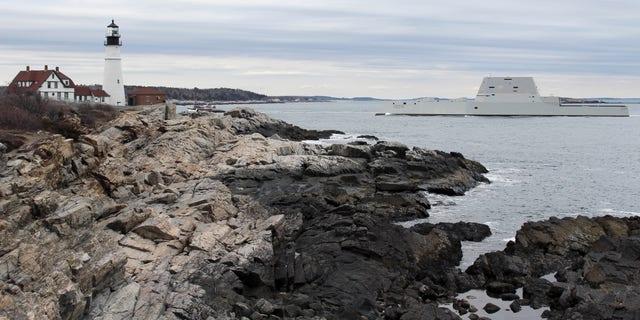 The USS Zumwalt passes Portland Headlight in Cape Elizabeth, Maine.