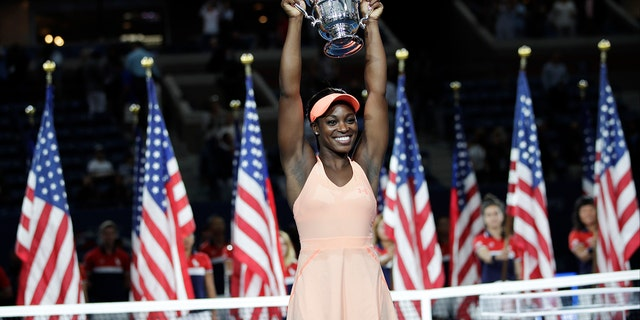 Sloane Stephens, of the United States, holds up the championship trophy after beating Madison Keys, of the United States, in the women's singles final of the U.S. Open tennis tournament, Saturday, Sept. 9, 2017, in New York. (AP Photo/Julio Cortez)
