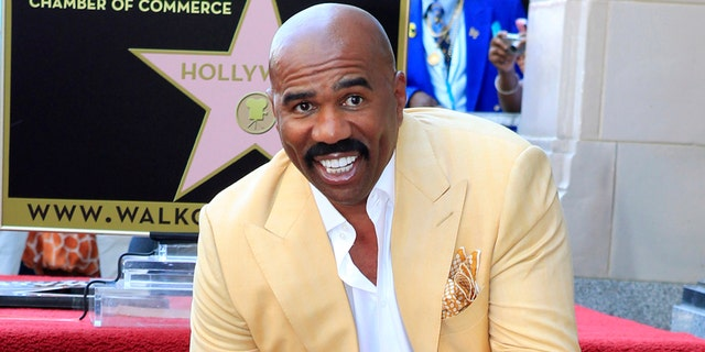 Comedian and actor Steve Harvey poses with his newly unveiled star on the Hollywood Walk of Fame in Hollywood May 13, 2013. REUTERS/Fred Prouser (UNITED STATES - Tags: ENTERTAINMENT) - RTXZL77