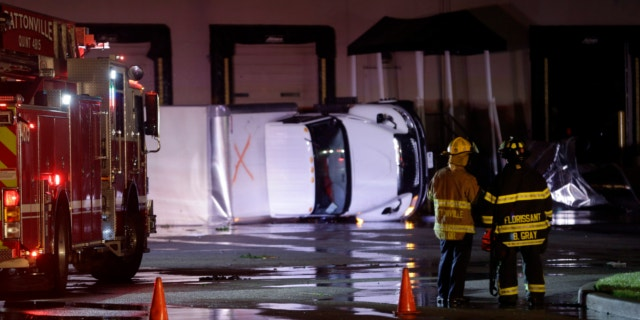 May 31, 2013: Rescue personnel stand near overturned trucks in an industrial park after strong storms moved through the area in St. Louis.