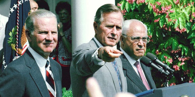 Aug. 20, 1991: President George H.W. Bush, flanked by Secretary of State James Baker III, left, and U. S. Ambassador to the Soviet Union Robert Strauss, points to a reporter during a Rose Garden press conference at the White House.