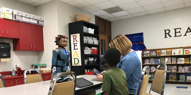 Facilitator Allison Thomlinson is using an iPad to prompt Milo if the student answered a question correctly or not. Williamston, SC.