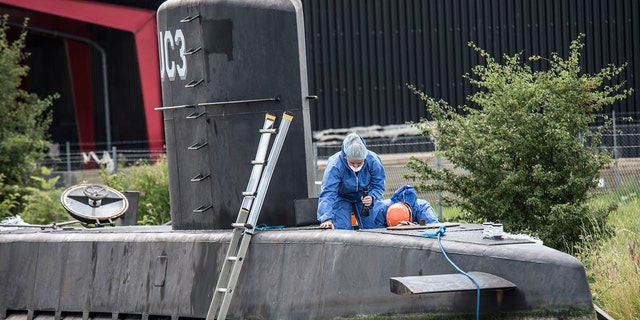 Police technicians on board the home-made submarine UC3 Nautilus on a pier in Copenhagen harbor.