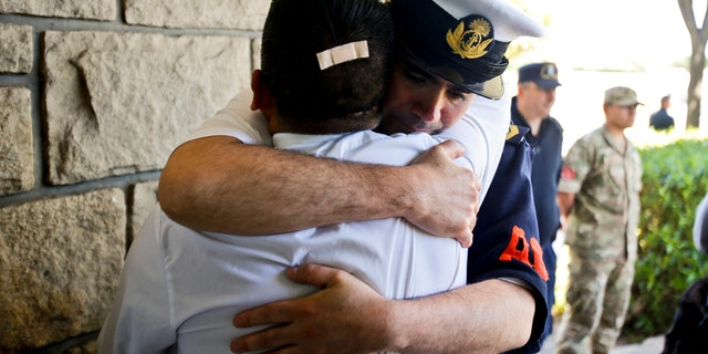 Argentine Navy officials embrace inside the Mar de Plata Naval Base after Argentina's Navy announced that a sound detected during the search for the missing ARA San Juan submarine is consistent with that of an explosion, in Mar de Plata, Argentina, Thursday, Nov. 23, 2017.