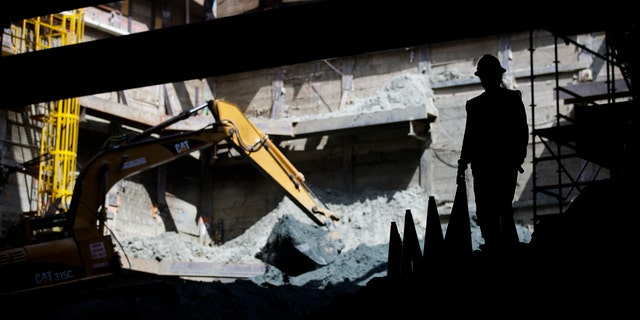 A worker stands near a backhoe at the construction site of the Metro Purple Line extension in Los Angeles.