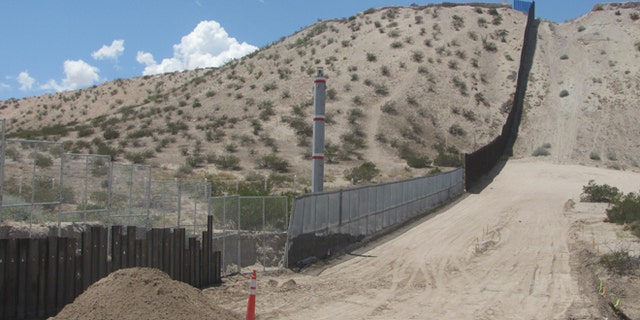 The old chainlink fence alongside SunlandPark is being replaced by an 18-foot high steel wall.