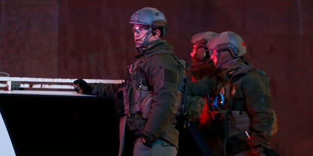 Denver SWAT team members survey Broncos fans celebrating Denver's win in the Super Bowl.