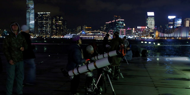 People set up telescopes on the waterfront for the super blue moon and eclipse in Hong Kong, China Jan. 31, 2018. (REUTERS/Bobby Yip)