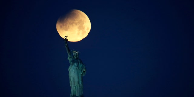 The Statue of Liberty is backdropped by a supermoon, Wednesday, Jan. 31, 2018, seen from the Brooklyn borough of New York. (AP Photo/Julio Cortez)