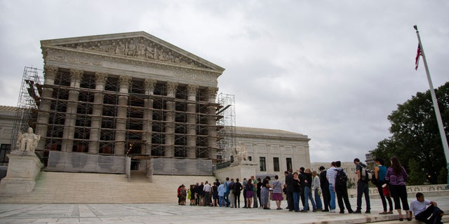 Oct. 7, 2013: People waiting in line  to enter the court in Washington. The Supreme Court justices are being asked to resolve a new clash of technology and privacy in the digital age.
